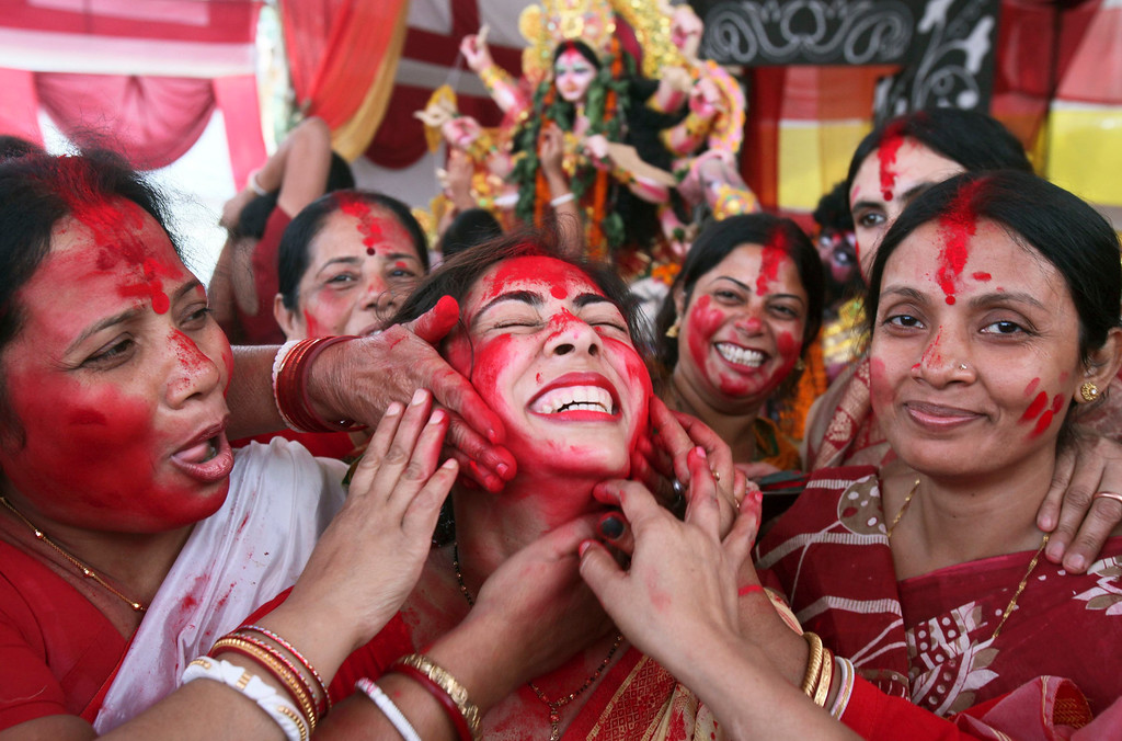 ". A Hindu woman reacts as she is smeared with ""sindhur\"", or vermillion powder, as part of a ritual on the last day of the Durga Puja festival in the northern Indian city of Chandigarh October 24, 2012. In Hindu mythology, Durga symbolises power and the triumph of good over evil. The Durga Puja is the biggest religious festival of Bengali Hindus. REUTERS/Ajay Verma"