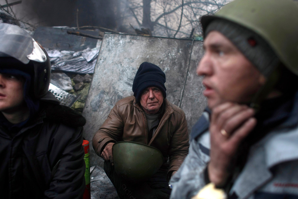. Anti-government protesters pause at  a barricade on the outskirts of Independence Square in Kiev, Ukraine, Thursday, Feb. 20, 2014.  (AP Photo/ Marko Drobnjakovic)