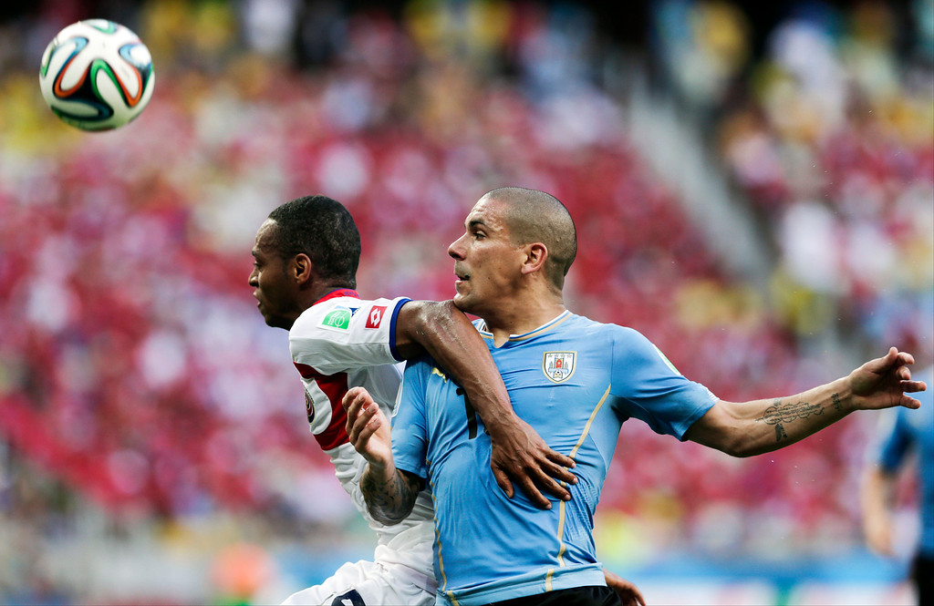 . Costa Rica\'s Junior Diaz, left, pushes off Uruguay\'s Maxi Pereira, right, during the group D World Cup soccer match between Uruguay and Costa Rica at the Arena Castelao in Fortaleza, Brazil, Saturday, June 14, 2014.  (AP Photo/Fernando Llano)
