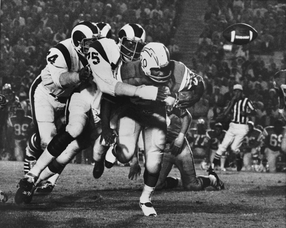 . In this Sept. 4, 1971 file photo, Los Angeles Ram\'s Deacon Jones, center, knocks the ball loose from San Diego Chargers\' Mike Garrett  in Los Angeles.  (AP Photo)