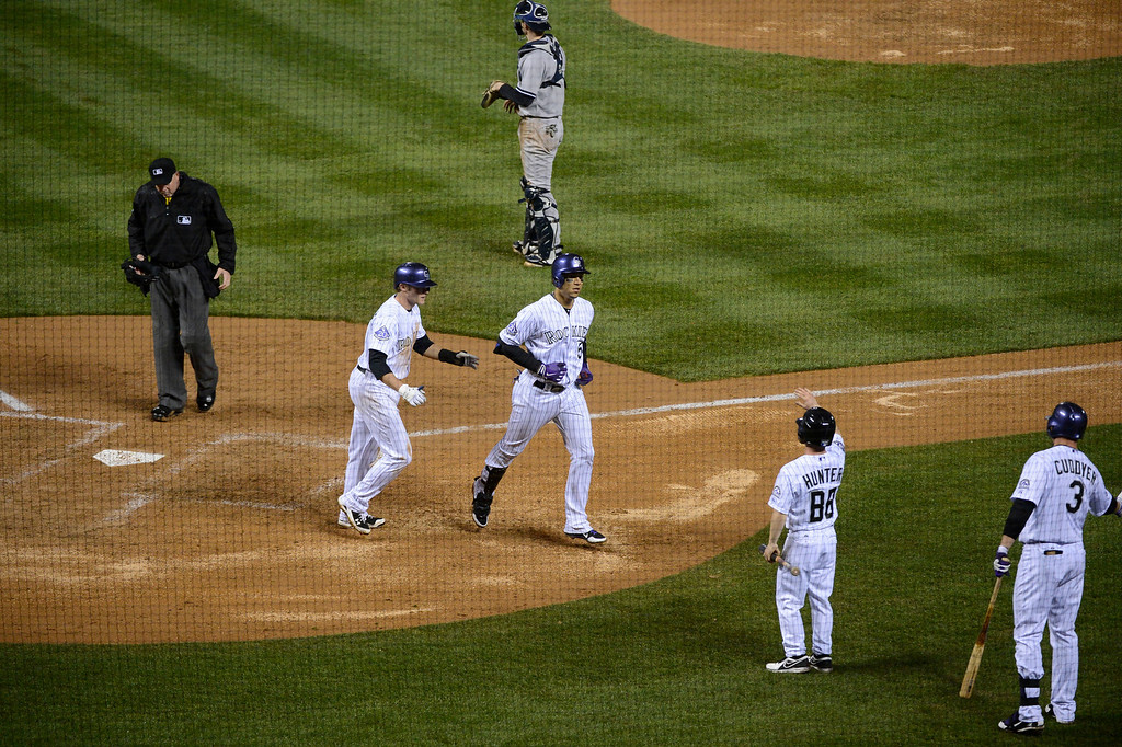 . DENVER, CO. - MAY 07: Carlos Gonzalez (5) of the Colorado Rockies is congratulated by Josh Rutledge (14) of the Colorado Rockies after hitting a two run home run in the sixth inning against the  New York Yankees May 7, 2013 at Coors Field. (Photo By John Leyba/The Denver Post)