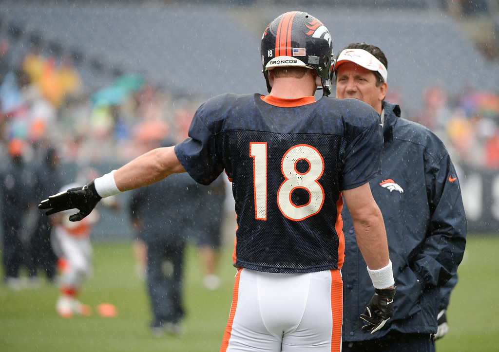 . Denver Broncos quarterback Peyton Manning (18) talks with quarter backs coach Greg Knapp during a rain day on day six of the Denver Broncos 2014 training camp July 30, 2014 at Sports Authority Field at Mile High Stadium.  (Photo by John Leyba/The Denver Post)