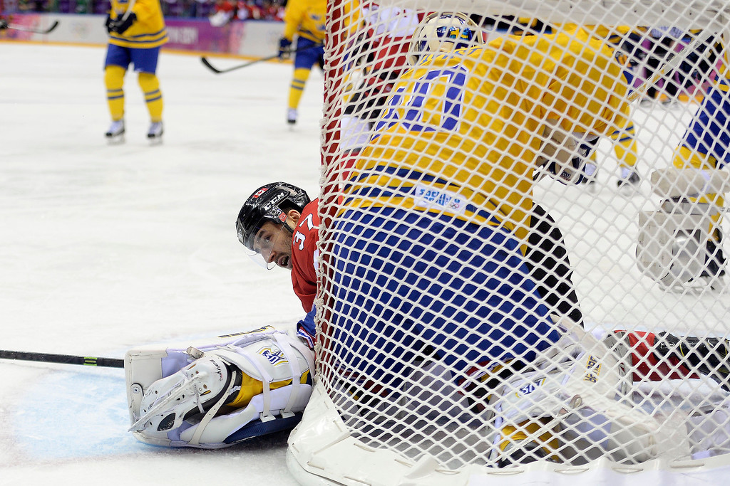 . Patrice Bergeron (37) of Canada falls in the crease as Henrik Lundqvist (30) of Sweden defends during the first period of the men\'s ice hockey gold medal game. Sochi 2014 Winter Olympics on Sunday, February 23, 2014 at Bolshoy Ice Arena. (Photo by AAron Ontiveroz/ The Denver Post)