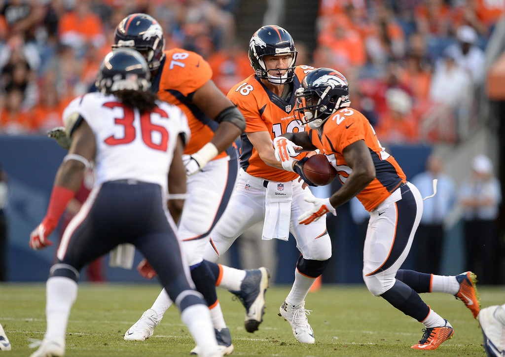. DENVER, CO - AUGUST 23: Denver Broncos quarterback Peyton Manning (18) hands off to Denver Broncos running back Ronnie Hillman (23) during the first quarter against the Houston Texans August 23, 2014 at Sports Authority Field at Mile High Stadium. (Photo by John Leyba/The Denver Post)
