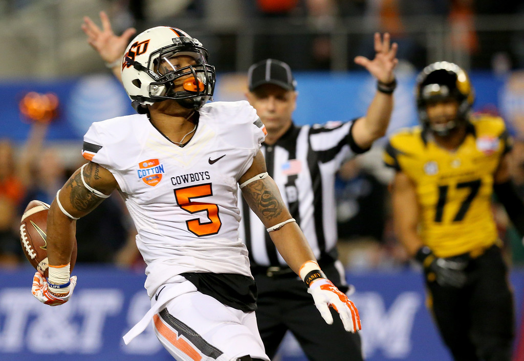 . ARLINGTON, TX - JANUARY 03:  Wide receiver Josh Stewart #5 of the Oklahoma State Cowboys scores a touchdown on a 40-yard catch in the first half while taking on the Missouri Tigers during the AT&T Cotton Bowl on January 3, 2014 in Arlington, Texas.  (Photo by Ronald Martinez/Getty Images)