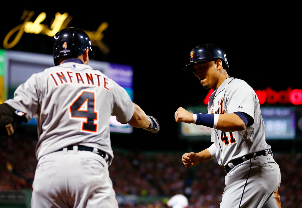 . Victor Martinez #41 celebrates with Omar Infante #4 of the Detroit Tigers after scoring in the second inning against the Boston Red Sox during Game Two of the American League Championship Series at Fenway Park on October 13, 2013 in Boston, Massachusetts.  (Photo by Jared Wickerham/Getty Images)