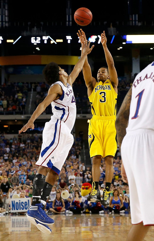 . Michigan Wolverines guard Trey Burke (3) shoots a three point basket over Kansas Jayhawks forward Kevin Young to tie the game during the second half in their South Regional NCAA men\'s basketball game in Arlington, Texas March 29, 2013.  REUTERS/Jim Young