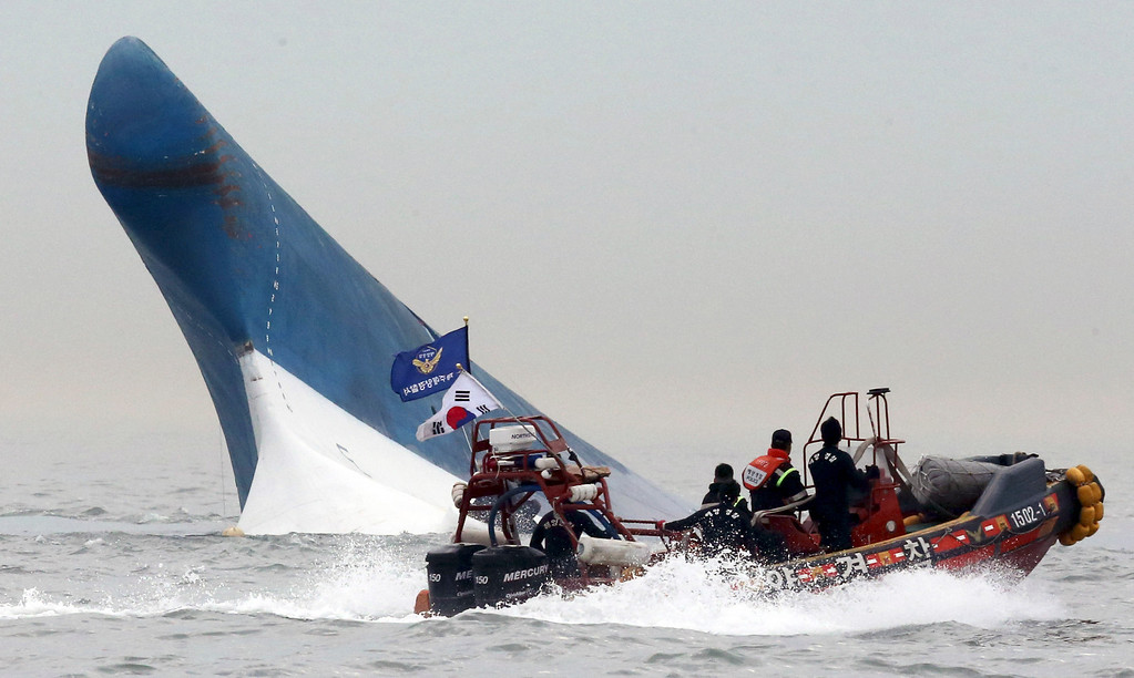 . South Korean coast guard officers try to rescue passengers from a ferry sinking in the water off the southern coast near Jindo, south of Seoul, South Korea, Wednesday, April 16, 2014.  (AP Photo/Yonhap)