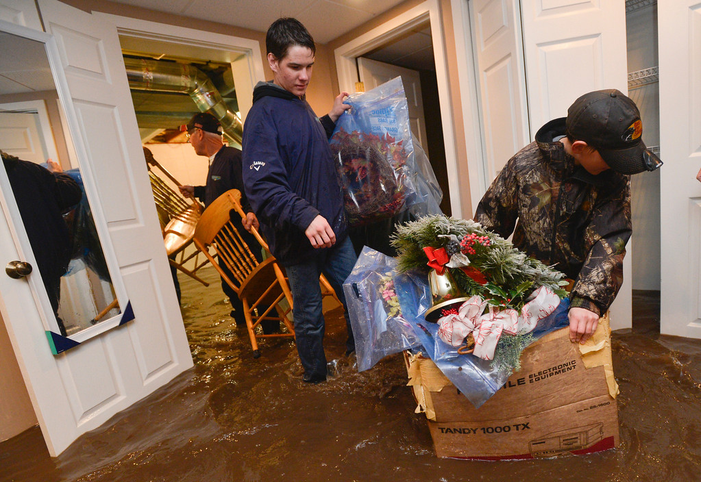 . Reuben Hodel, 12, right, and his brother Max Hodel, 15, help to save belongings of homeowner Ross Gingrich of Roakoke, Ill. early Thursday, April 18, 2013,  as flood waters from nearby West Branch Panther Creek caused by heavy rain  flooded homes overnight.  The National Weather Service expected a storm system moving over Illinois would dump about three inches of rain in the area. (AP Photo/Journal Star, Ron Johnson)