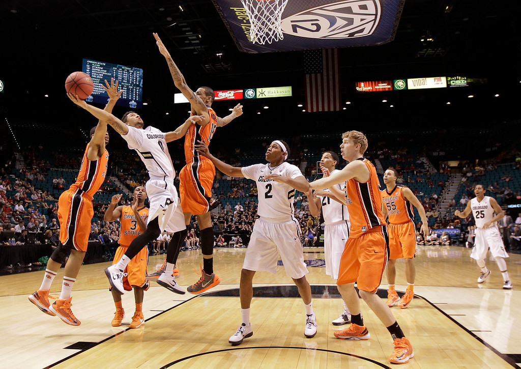 . Colorado\'s Askia Booker (0) shoots against Oregon State\'s Eric Moreland (15) and Devon Collier (44) in the first half during a Pac-12 tournament NCAA college basketball game on Wednesday, March 13, 2013, in Las Vegas. Colorado won 74-68. (AP Photo/Julie Jacobson)