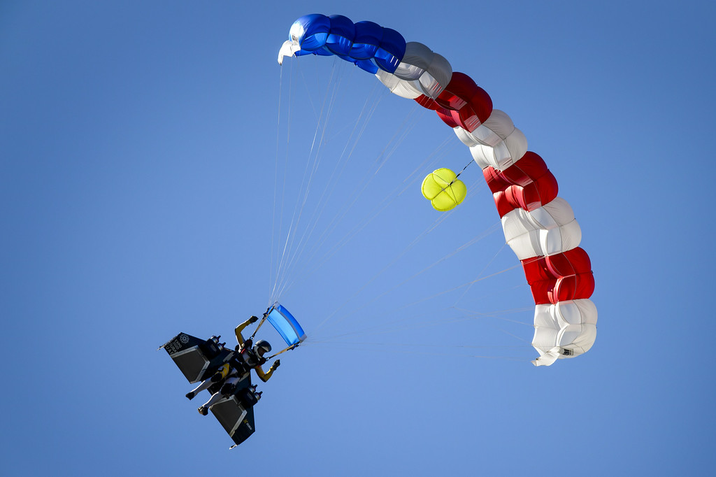 """. Swiss pilot Yves Rossy known as the \""""Jetman\"""" lands with a parachute after his flight with his jet-powered two meters wingspan wing attached to his back during the first day of the AIR14 air show on August 30, 2014 in Payerne, western Switzerland.  AFP PHOTO / FABRICE  COFFRINI/AFP/Getty Images"""