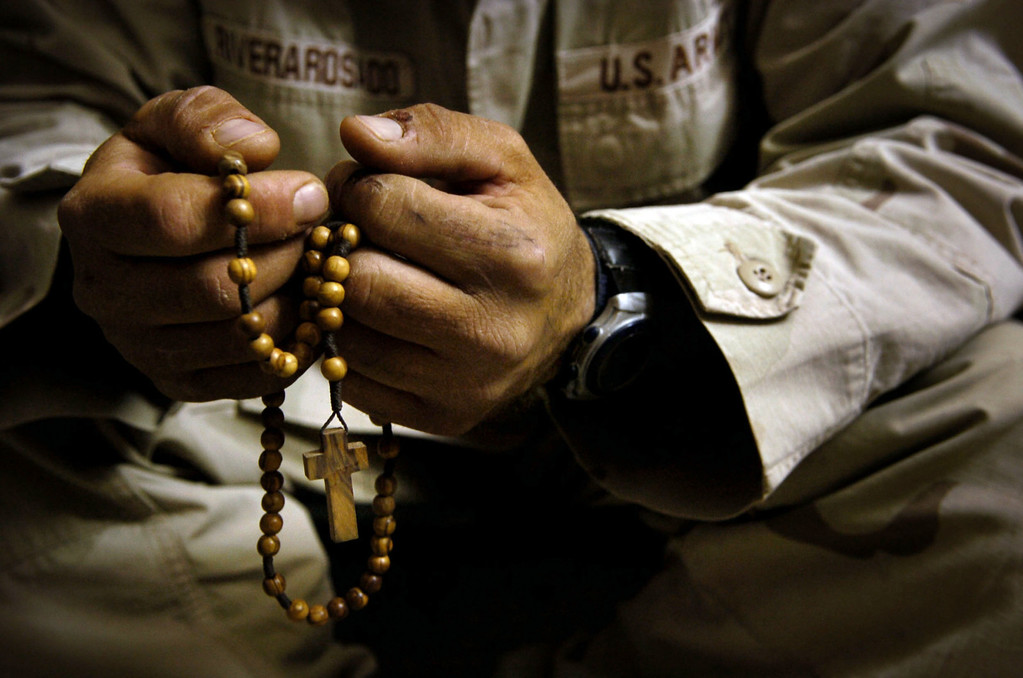 . Support Squadron -SPC Carlos Riverarosado, of Narantito, Puerto Rico sits on his cot with his Rosary Beads at camp Striker in Iraq. He said spirituality had always been a big part of his life. He prays the Rosary every night at 8:00 PM. (Craig F. Walker/The Denver Post)