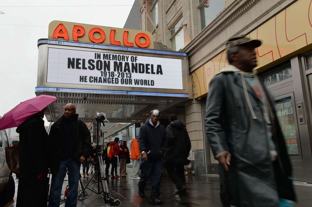 ". The marquee at the Apollo Theater in Harlem displays a memorial sign after the death of Nelson Mandela, former South African president and anti-apartheid leader, on December 6, 2013 in New York. The world on Friday mourned Mandela, who was hailed universally as an ""incredible gift\"" to humanity. Mandela\'s \""rainbow nation\"" awoke to a future without its founding father and its first black president, after he died late on December 5 aged 95 at his Johannesburg home surrounded by friends and family. AFP PHOTO/Stan HONDASTAN HONDA/AFP/Getty Images"