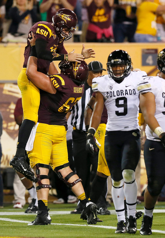 . Arizona State\'s Taylor Kelly, left, celebrates his touchdown run with Kody Koebensky as Colorado\'s Tedric Thompson (9) walks away during the first half of an NCAA college football game Saturday Oct. 12, 2013, in Tempe, Ariz. (AP Photo/Ross D. Franklin)