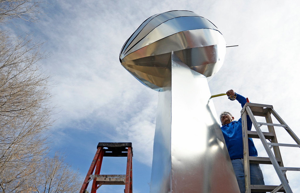 . Carlos Tovar, an employee at Frontier Roofing System in east Denver, work on making a 14-foot Vince Lombardi Trophy, January, 26 2014.  (Photo by RJ Sangosti/The Denver Post)