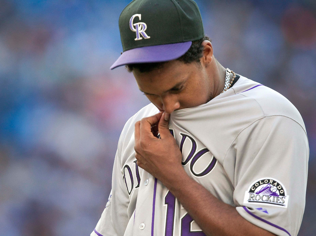 . Colorado Rockies starting pitcher Juan Nicasio walks off the field at the end of the first inning after giving up a three-run home run to the Toronto Blue Jays during their interleague MLB baseball game in Toronto June 19, 2013.   REUTERS/Fred Thornhill