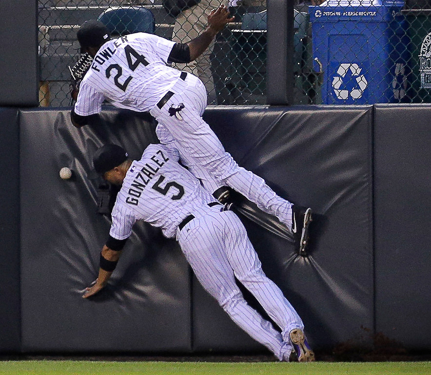 . Colorado Rockies outfielder Dexter Fowler (24) collides with teammate Carlos Gonzalez as they chased a fly ball hit by Washington Nationals\' Ryan Zimmerman for a double in the sixth inning of a baseball game on Wednesday, June 12, 2013, in Denver. (AP Photo/Joe Mahoney)