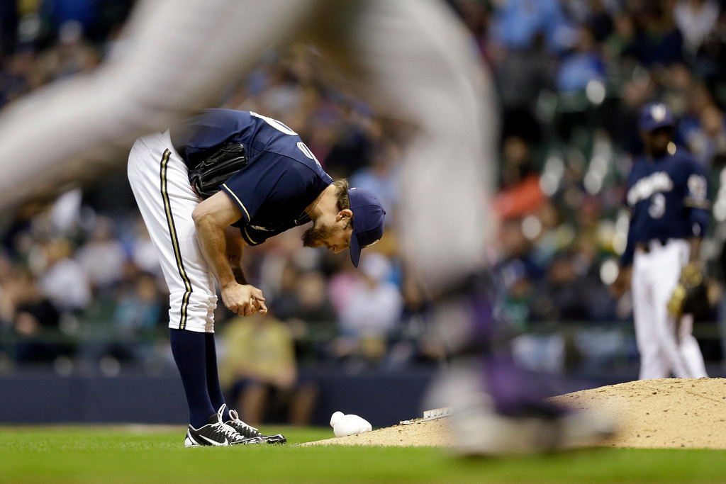 . Milwaukee Brewers pitcher John Axford reacts as Colorado Rockies\' Michael Cuddyer rounds the bases after his two-run home run during the ninth inning of a baseball game, Wednesday, April 3, 2013, in Milwaukee. (AP Photo/Jeffrey Phelps)