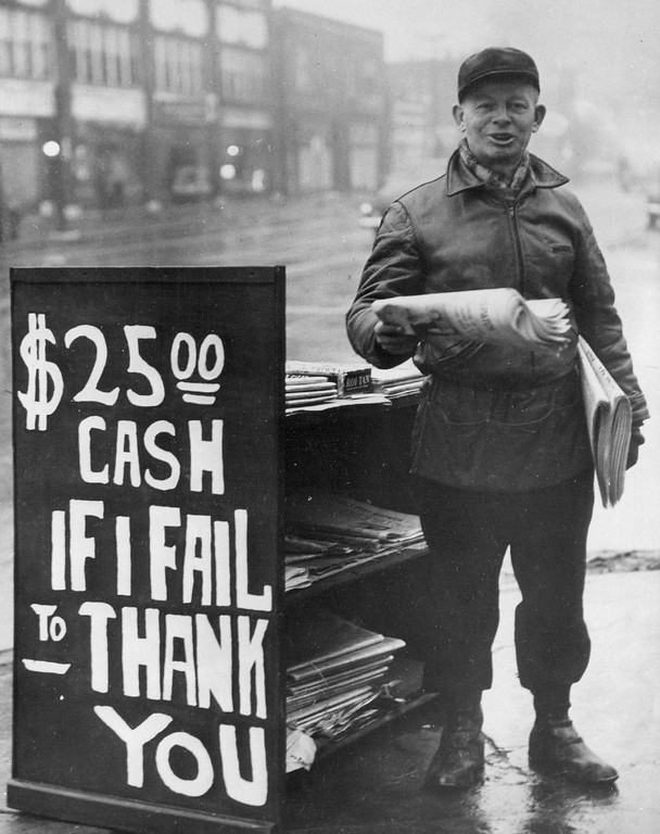 . Ted D. Gatlin, 47-year-old St. Louis news vendor, displays a sign on his stand offering a cash reward if he fails to thank a customer. No one has been able to collect; some get angry when they fail. August, 1952. (Wide World Photo)