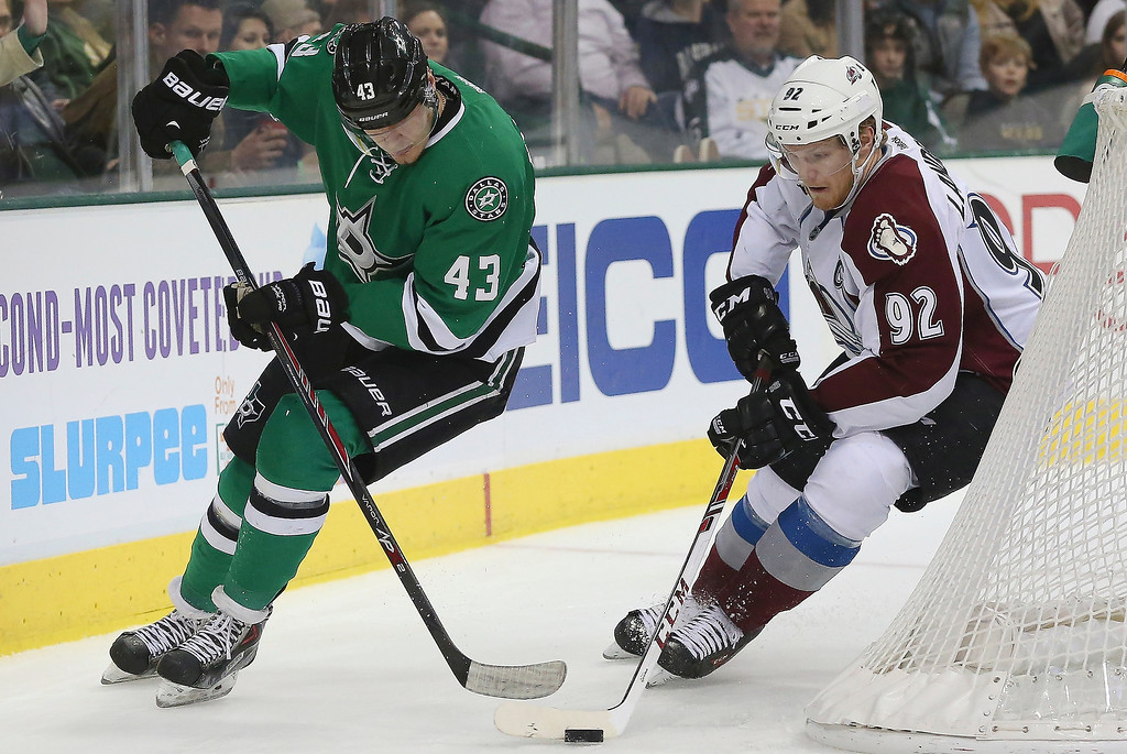 . Gabriel Landeskog #92 of the Colorado Avalanche skates the puck against Valeri Nichushkin #43 of the Dallas Stars in the first period at American Airlines Center on December 17, 2013 in Dallas, Texas.  (Photo by Ronald Martinez/Getty Images)