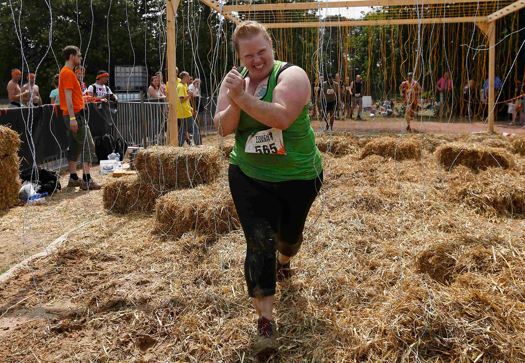 """. Heather Cozad of the U.S. runs through the \""""Electroshock Therapy\"""" obstacle made of hanging electrical wire holding some 10,000 Volts in the finish of the \""""Tough Mudder\"""" endurance event series in the Fursten Forest, a former British Army training ground near the north-western German city of Osnabrueck July 13, 2013. The hardcore but un-timed event over 16 km (10 miles) was designed by British Special Forces to test mental as well as physical strength. Some 4,000 competitors had to overcome obstacles of common human fears, such as fire, water, electricity and heights. REUTERS/Wolfgang Rattay"""