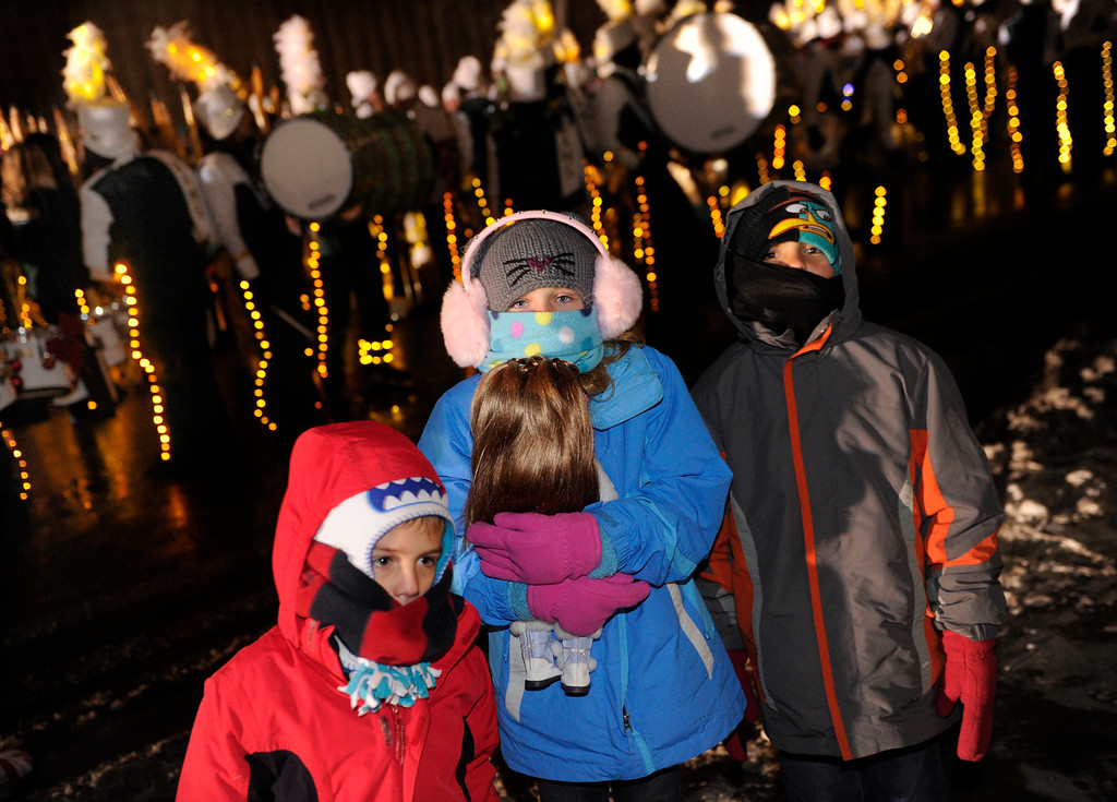 . DENVER, CO. - DECEMBER 06: Michael Lucero, left, his sister Bella, center, and his brother Dante, right, were bundled up as the 9News Parade of Lights kicked off Friday night, December 6, 2013. The siblings are from Albuquerque, New Mexico. The weather for the parade was clear but temperatures dipped below zero. Photo By Karl Gehring/The Denver Post