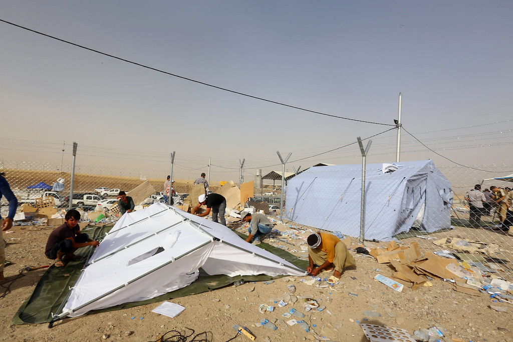 . Iraqi refugees from Mosul set up a tent at Khazir refugee camp outside Irbil, 217 miles (350 kilometers) north of Baghdad, Iraq, Wednesday June 11, 2014. The Islamic State of Iraq and the Levant, the al-Qaida breakaway group, on Monday and Tuesday took over much of Mosul in Iraq and then swept into the city of Tikrit further south. An estimated half a million residents fled Mosul, the economically important city. (AP Photo)