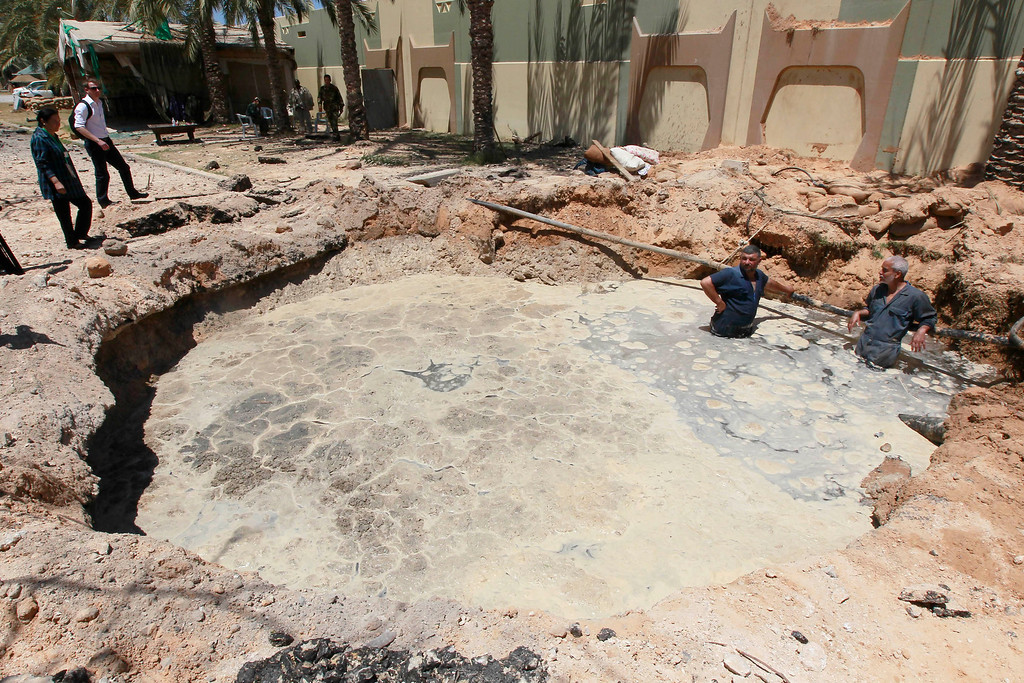 . A crater, which the Libyan government said was caused by coalition air strikes, is seen at an area in Bab al-Aziziyah compound in Tripoli May 12, 2011. Libyan officials, who showed reporters around the scene of the air strike, at Gaddafi\'s Bab al-Aziziyah compound, said three people were killed and 25 wounded. REUTERS/Louafi Larbi