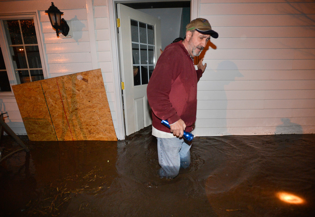 . Bob Zehr wades through flood waters surrounding the home Ross and Nancy Gingrich of Roanoke, Ill.  early Thursday, April 18, 2013,  as friends helped to save belongings and evacuate residents living near the West Branch Panther Creek in the town after heavy rains flooded several homes.  (AP Photo/Journal Star, Ron Johnson)