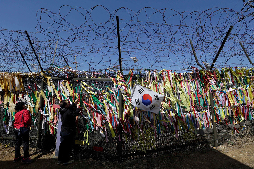 . A tourist hangs a ribbon with messages wishing for the reunification of the two Koreas, at the Imjingak Pavilion near the border village of Panmunjom, which has separated the two Koreas since the Korean War, in Paju, north of Seoul, South Korea, Sunday, April 14, 2013. As the world watches to see what North Korea\'s next move will be in a high-stakes game of brinksmanship with the United States, residents of its capital aren\'t hunkering down in bunkers and preparing for the worst. Instead, they are out on the streets en masse getting ready for the birthday of national founder Kim Il Sung - the biggest holiday of the year. (AP Photo/Lee Jin-man)