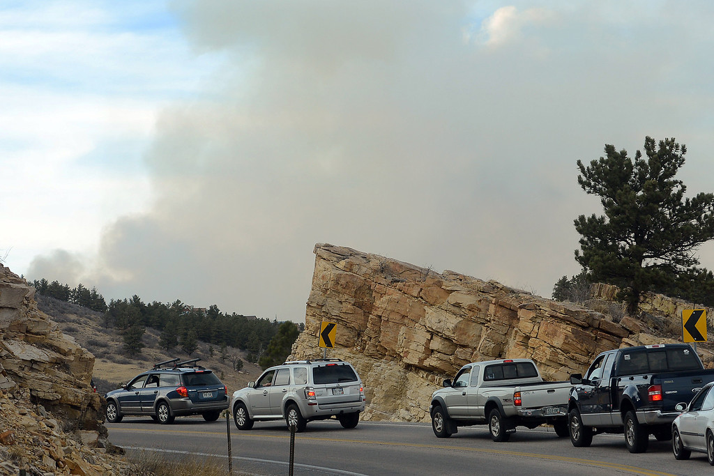 . A plume of smoke from the Galena fire is visible in the distance as a line of cars waits on Friday, March 15, 2013 to continue on the road at the south end of Horsetooth Reservoir. (Steve Stoner/Loveland Reporter-Herald)