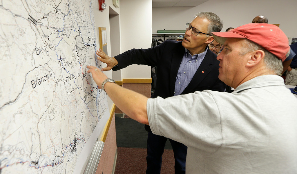 . Washington Gov. Jay Inslee, left, is briefed on the Chiwaukum Creek Fire by incident commander Ed Lewis, right, Friday, July 18, 2014, in Leavenworth, Wash. (AP Photo/Ted S. Warren)