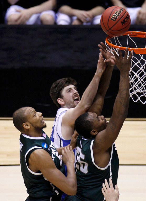 . Duke Blue Devils forward Ryan Kelly (C) reaches for a rebound against Michigan State Spartans forwards Adreian Payne (L) and Derrick Nix during their Midwest Regional NCAA men\'s basketball game in Indianapolis, Indiana, March 29, 2013. REUTERS/Matt Sullivan