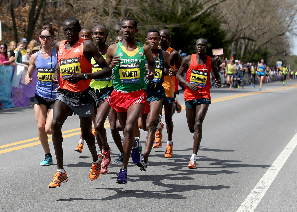 . Elite runners lead by Dennis Kimetto, of Kenya, and Markos Geneti, of the United States, pass Wellesley College during the 118th Boston Marathon Monday, April 21, 2014 in Wellesley. (AP Photo/Mary Schwalm)