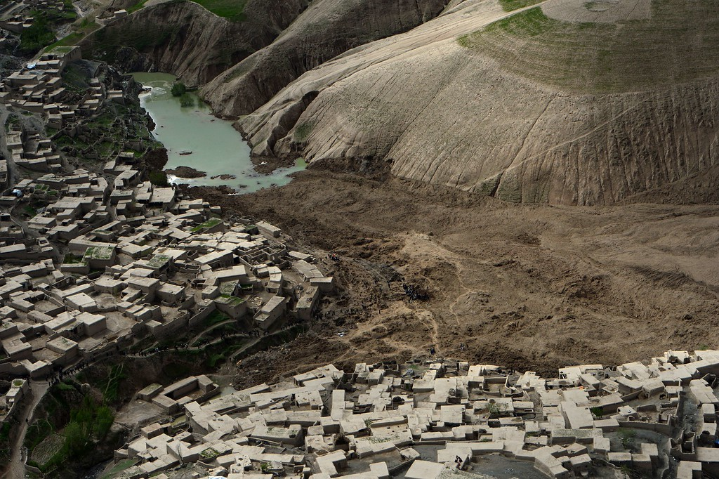 . Afghan villagers dig through the mud and rocks of a landslide in Aab Bareek village at Argo district of Badakhshan on May 5, 2014.  AFP PHOTO/WAKIL  KOHSAR/AFP/Getty Images