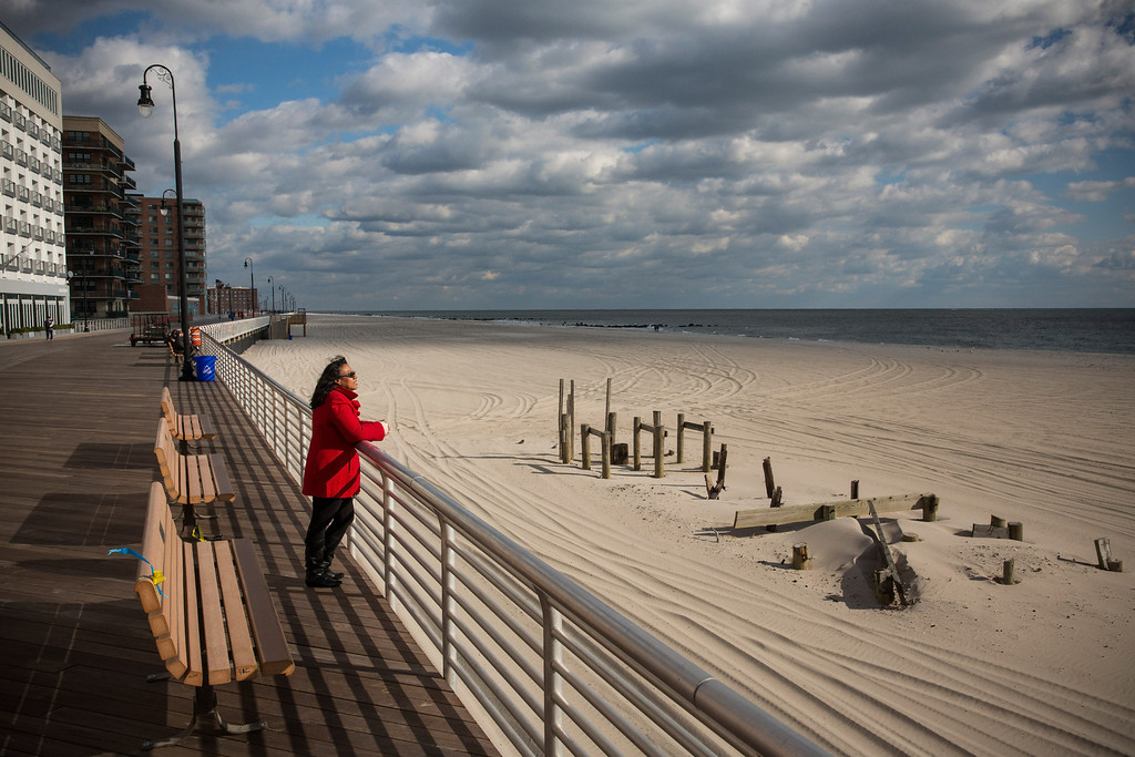 . LONG BEACH, NY - OCTOBER 25:  A woman who only identified herself as Gigi looks out to see from the Long Beach boardwalk on October 25, 2013 in Long Beach, New York. The Long Beach boardwalk was severely damaged by Superstorm Sandy last year, which killed 285 people and caused billions of dollars in damage, though the boardwalk reopened today. Long Beach\'s new boardwalk is made of Brazilian hardwood and is estimated to have a lifespan of 30-40 year; the previous boardwalk was only scheduled to last  three to seven years.  (Photo by Andrew Burton/Getty Images)