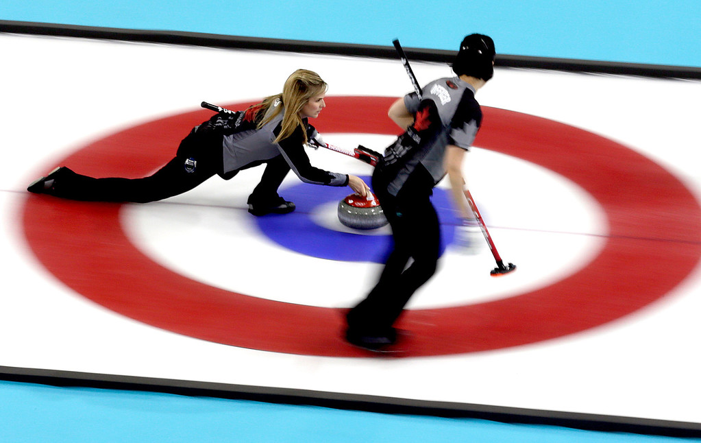 . Canada\'s skip Jennifer Jones delivers the rock while Jill Officer prepares to sweep the ice during the women\'s curling competition against Denmark at the 2014 Winter Olympics, Thursday, Feb. 13, 2014, in Sochi, Russia. (AP Photo/Wong Maye-E)