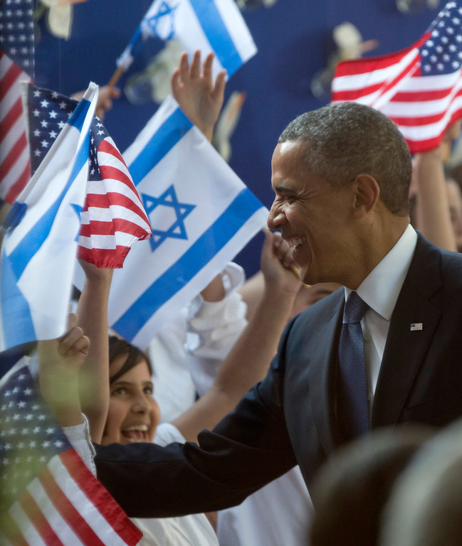 . President Barack Obama is greeted by children waving Israeli and American flags as he arrives at the residence of Israeli President Shimon Peres, Wednesday, March 20, 2013, in Jerusalem. (AP Photo/Carolyn Kaster)