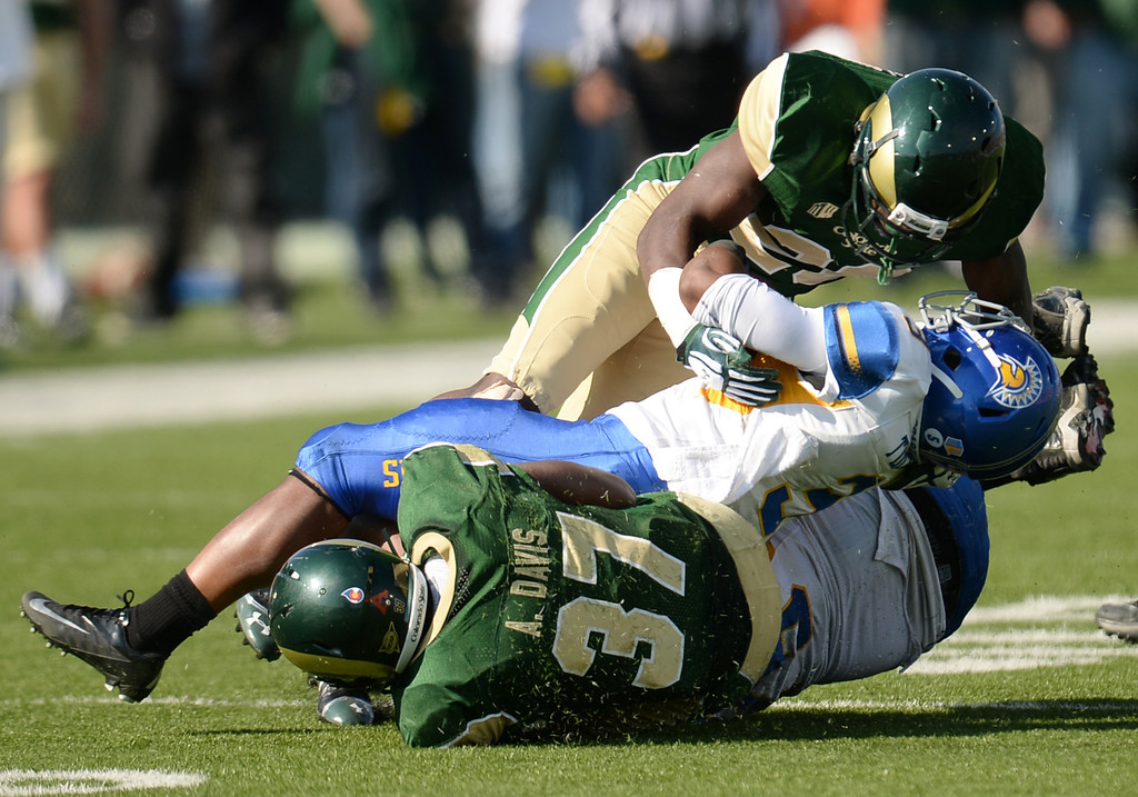 . FORT COLLINS, CO - OCTOBER 12 : Kevin Pierre-Louis (26), top, and Aaron Davis (37) of Colorado State (3), tackle Thomas Tucker of San Jose State (3) in the 1st quarter of the game at Hughes Stadium. Fort Collins. Colorado. October 12, 2013. Tucker was injured in the play. San Jose won 34-27. (Photo by Hyoung Chang/The Denver Post)