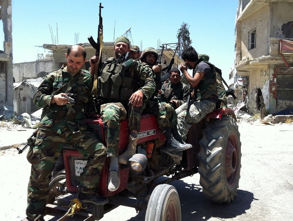 . Syrian army\'s soldiers sit on a tractor holding their weapons on June 5, 2013 in the city of Qusayr in Syria\'s central Homs province, after the Syrian government forces seized total control of the city and the surrounding region. The Syrian army ousted rebels from the strategic town of Qusayr after a blistering 17-day assault led by Hezbollah fighters, scoring a major battlefield success in a war that has killed at least 94,000 people.   AFP PHOTO / STR-/AFP/Getty Images