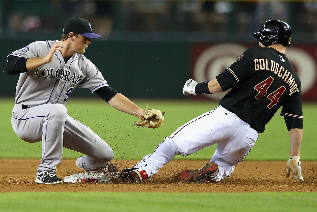 . Paul Goldschmidt #44 of the Arizona Diamondbacks safely slides into second base under the tag from infielder DJ LeMahieu #9 of the Colorado Rockies during the third inning of the MLB game at Chase Field on July 7, 2013 in Phoenix, Arizona.  (Photo by Christian Petersen/Getty Images)