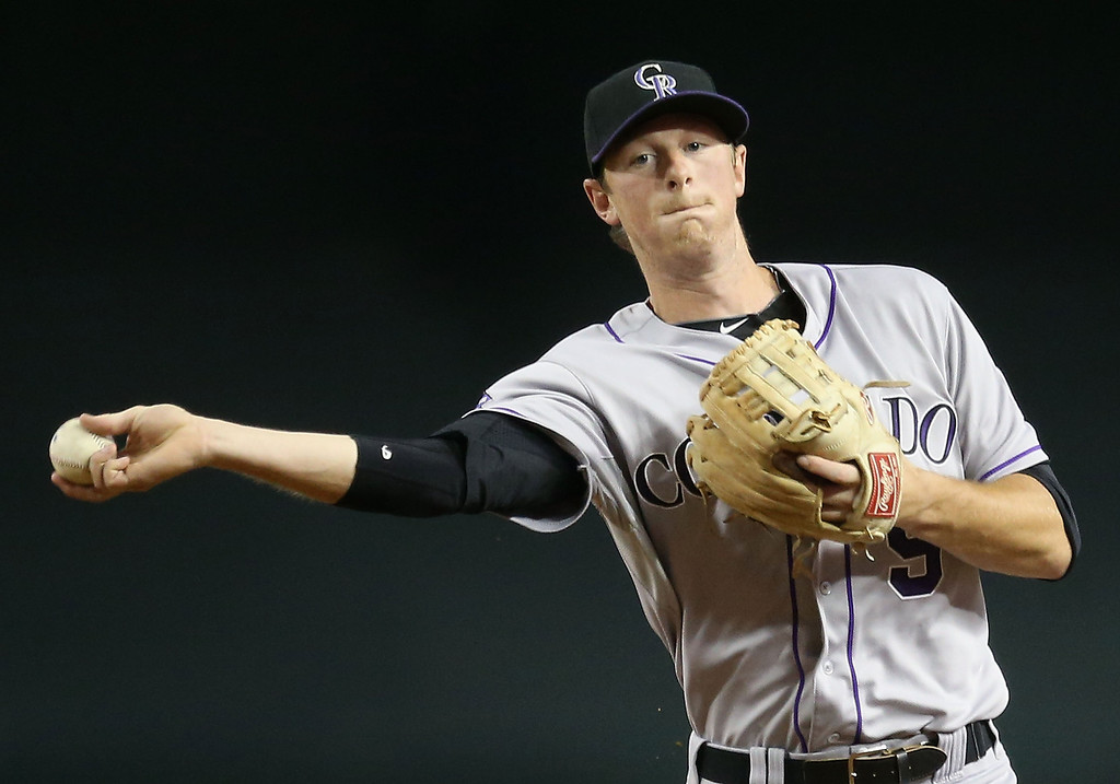 . PHOENIX, AZ - JULY 05:  Infielder DJ LeMahieu #9 of the Colorado Rockies fields a ground ball out against the Arizona Diamondbacks during the MLB game at Chase Field on July 5, 2013 in Phoenix, Arizona.  (Photo by Christian Petersen/Getty Images)