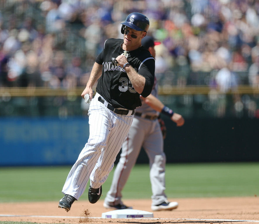 . Colorado Rockies\' Justin Morneau rounds third base to score on a double by Nolan Arenado against the Minnesota Twins in the first inning of an interleague baseball game in Denver on Sunday, July 13, 2014. (AP Photo/David Zalubowski)