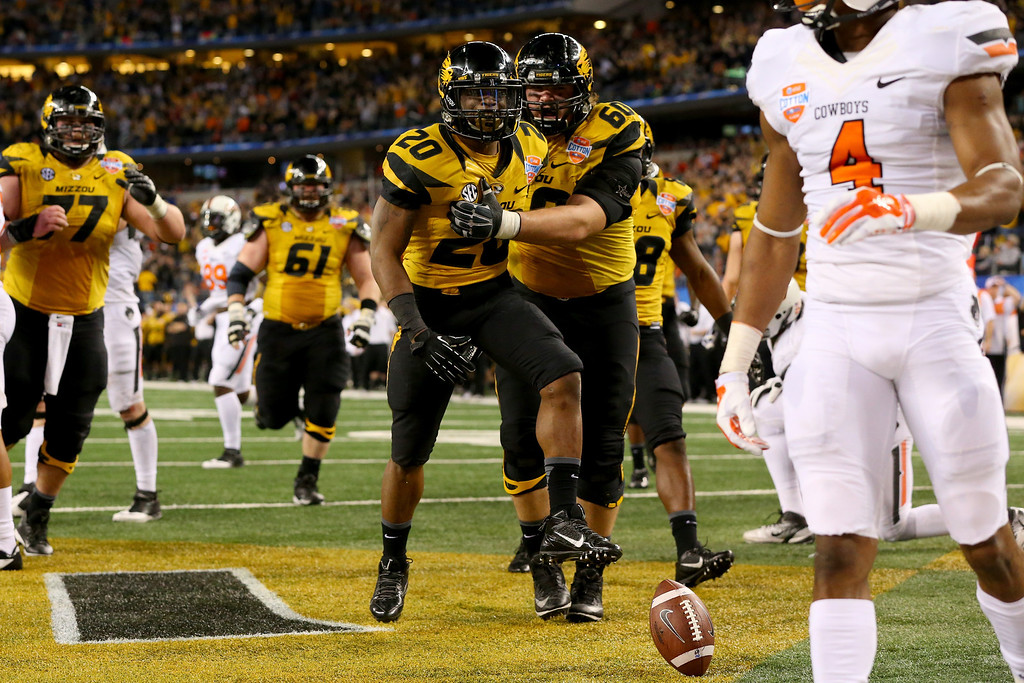 . ARLINGTON, TX - JANUARY 03:  Running back Henry Josey #20 of the Missouri Tigers celebrates with Connor McGovern #60 after scoring on a 20-yard touchdown run in the fourth quarter against the Oklahoma State Cowboys during the AT&T Cotton Bowl on January 3, 2014 in Arlington, Texas.  (Photo by Ronald Martinez/Getty Images)