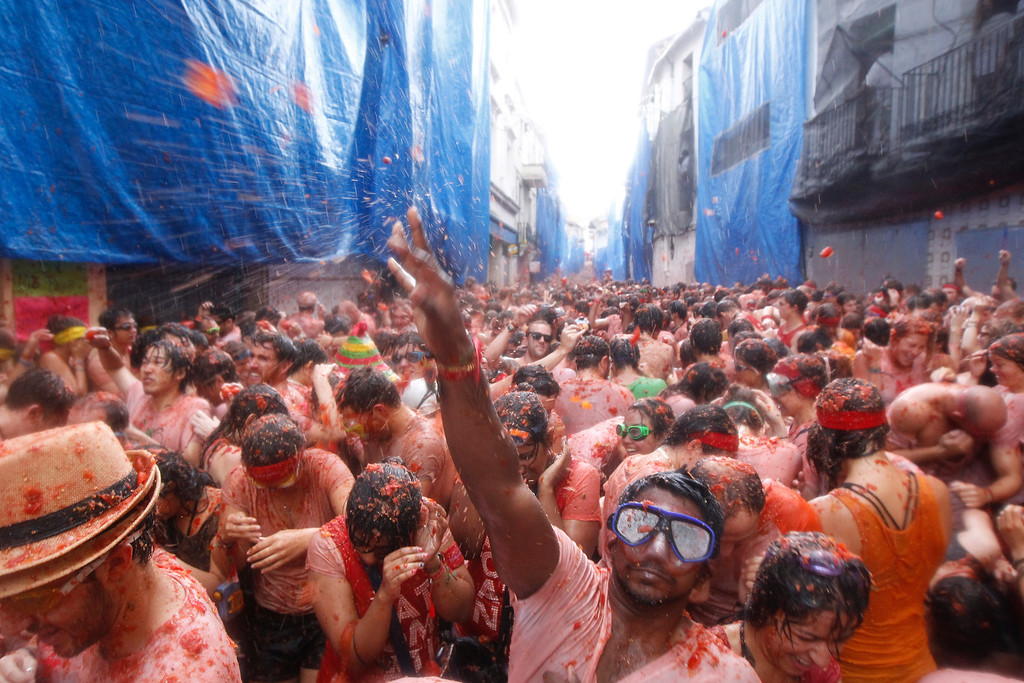 """. Crowds of people throw tomatoes at each other during the annual \""""tomatina\"""" tomato fight fiesta in the village of Bunol, 50 kilometers outside Valencia, Spain, Wednesday, Aug. 28, 2013. Thousands of people are splattering each other with tons of tomatoes in the annual \""""Tomatina\"""" battle in recession-hit Spain, with the debt-burdened town charging participants entry fees this year for the first time. Bunol town says some 20,000 people are taking part in Wednesday\'s hour-long street bash, inspired by a food fight among kids back in 1945. Participants were this year charged some 10 euros ($13) to foot the cost of the festival. Residents do not pay. (AP Photo/Alberto Saiz)"""