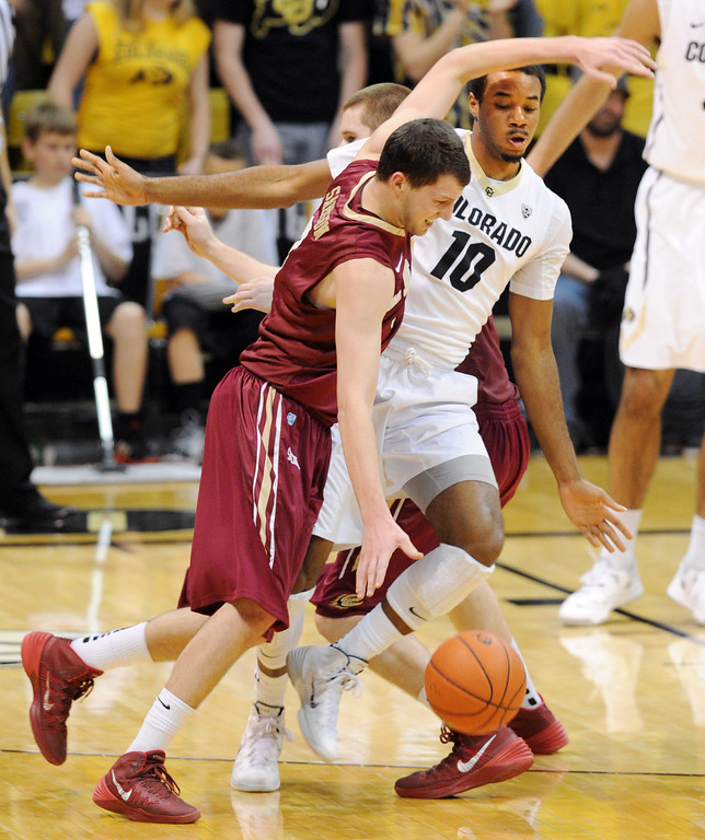 . Tanner Samson of Elon tries to get rid of Tre\'Shawn Fletcher with a screen during the second half of the December 13, 2013 game in Boulder. (Cliff Grassmick/Boulder Daily Camera)