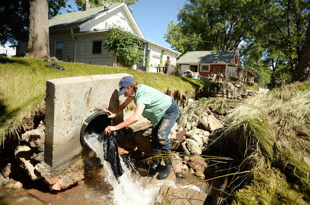 . LONGMONT, CO - September 18 : Barbara Hull washes a shirt by the ditch in the back yard of her house damaged by flooding near the corner of 75th St. and Hygiene Rd. in Longmont, Colorado. September 18, 2013.  (Photo by Hyoung Chang/The Denver Post)