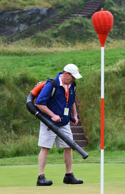 . A grounds keeper with a leaf blower disperses water from the green of the 17th hole, during the first round of the 113th US Open Golf Championship, at Merion Golf Club in Haverford. Photo by Tom Kelly IV Daily Local News