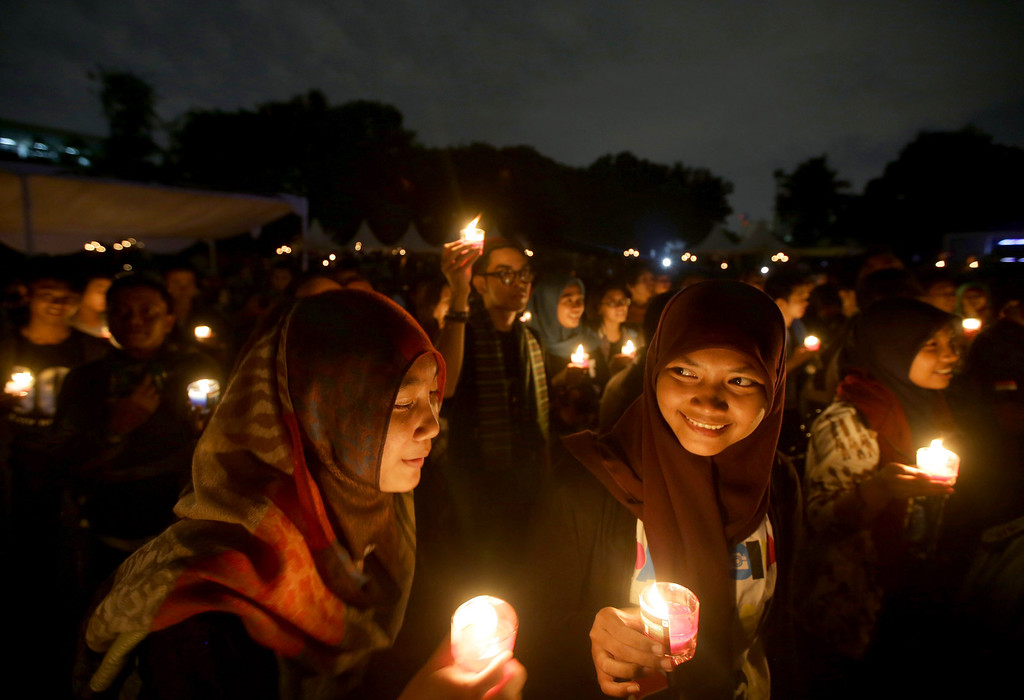 ". Muslim women light candles during the ""EarthHour\"" in Jakarta, Indonesia, Saturday, March 23, 2013. Hundreds of people gathered in Jakarta Friday to observe the global event that encourages people to turn off their lights for 60 minutes. (AP Photo/Dita Alangkara)"