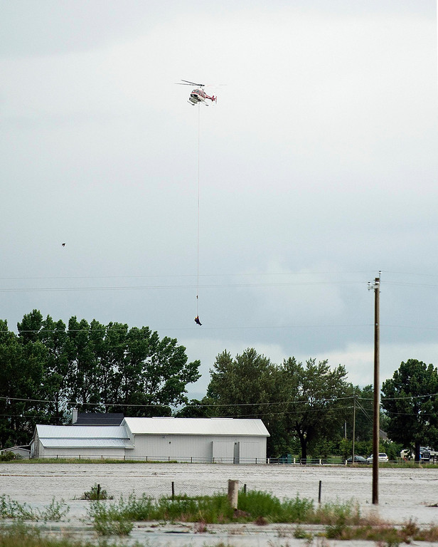 . A person stranded on the roof of a vehicle is airlifted to safety by a helicopter in High River in Alberta province June 20, 2013. A state of emergency has been issued for the town of High River, which is being evacuated due to floods. REUTERS/Mike Sturk